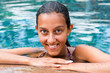 Smiling Indian Woman Leaning on the Pool Edge