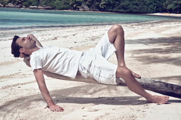 Young man relaxing on an old tree at the beach