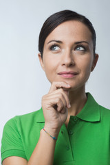 Smiling woman thinking with hand on chin