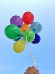 Hand hält viele bunte Ballons