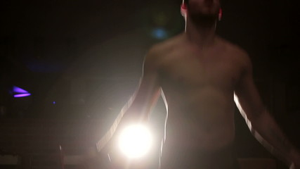 Man skipping on rope in dark