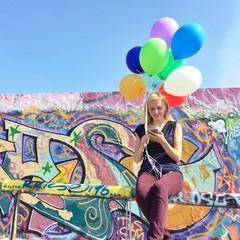 Mädchen mit Smartphone und Ballons