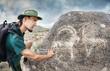 Man touching petroglyph with goat