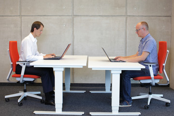 two men coworking in correct sitting posture on chairs in office
