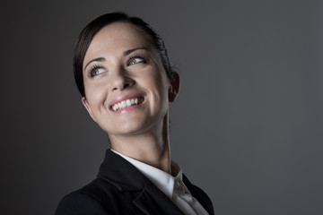 Confident female manager posing on dark background