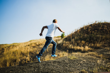 Young man in casual wear running uphill