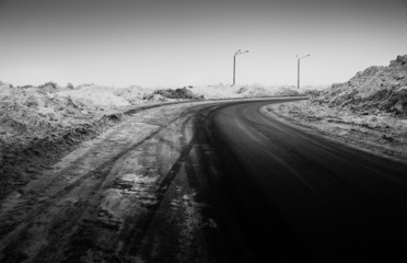 Snow-covered road, the marks of wheels, black and white  photo