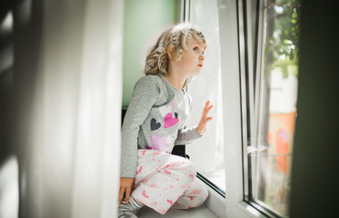 Little girl watching out of a window