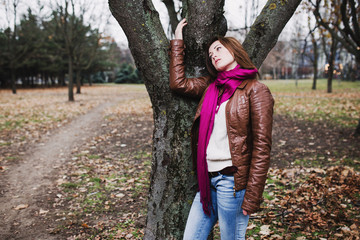 Pensive young  brunette girl standing near tree in autumn park