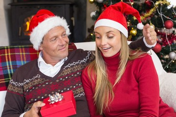 Loving couple in santa hat with gift