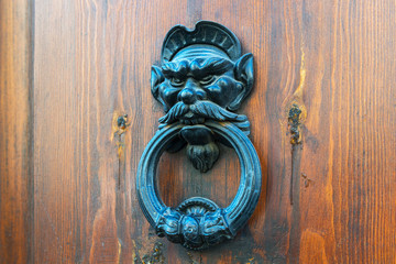 Ancient door knocker on a wooden door in Rome