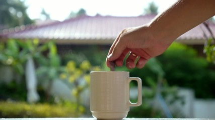 Male Hand Stirs Steaming Cup of Tea Outdoors. Slow Motion.