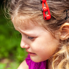 Cute little girl crying on the background of green grass.