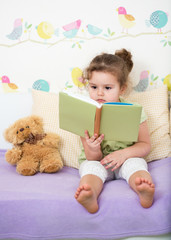 kid girl reading story for teddy bear