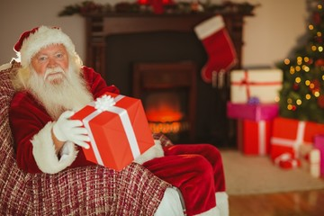 Cheerful santa claus offering a gift