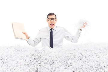 Man holding folder in a pile of shredded paper