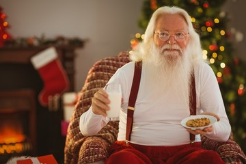 Santa holding glass of milk and plate with cookie