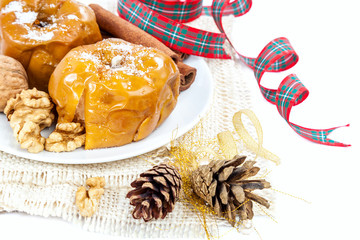 Baked apples with nuts and cinnamon on white background.