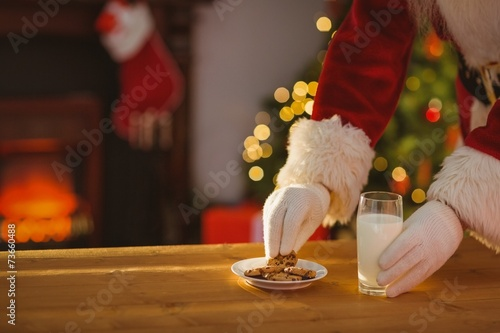 Santa claus picking cookie and glass of milk - 73660488