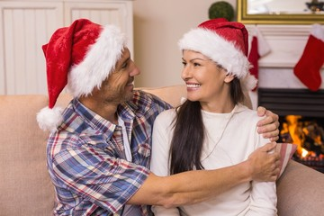 Festive couple in santa hat hugging on the couch
