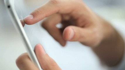 Closeup of hand sliding on digital tablet