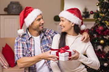 Happy couple in santa hat holding present