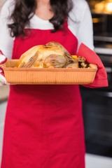 Mid section of woman holding roast turkey