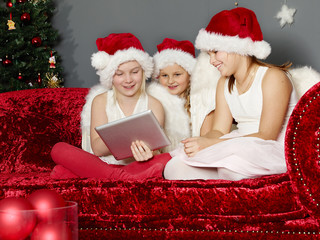 Cute girls with tabletpc on christmas