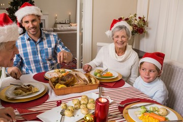 Father in santa hat serving roast turkey at christmas