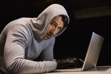 Man in hood jacket hacking a laptop while looking at camera