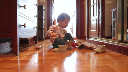 Baby girl trying put on shoes sitting over wooden floor