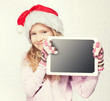 Child in christmas hat with tablet
