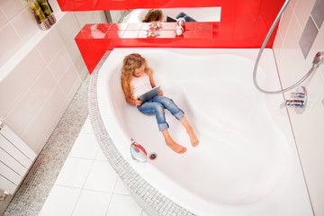 Girl hiding in the bathroom, playing in tablet