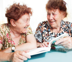 Two seniors reading book