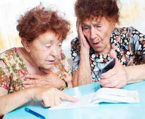 Two old women consider receipts