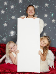 Cute girls with whiteboard for christmas