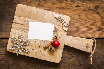 Blank card on cutting board with christmas decorations