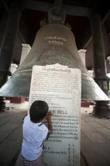 Boy reading plaque of Mingun Bell in Myanmar.