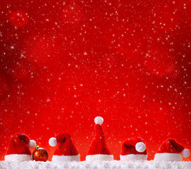 Five Christmas hats  isolated on red background.