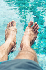 Male feet resting on crystal clear water