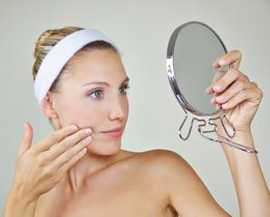 Frau schaut im Spiegel nach Falten