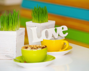 Still life with love wooden word on colorful coffee cups