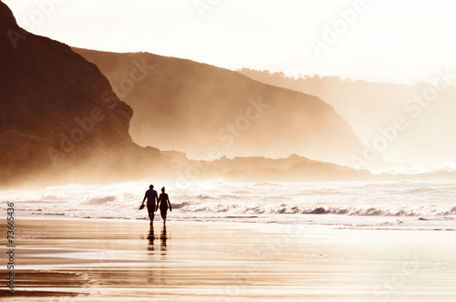couple walking on beach with fog - 73665436