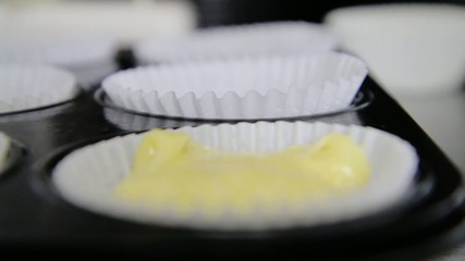 Vanilla or lemon cupcake batter being poured into cupcake form.