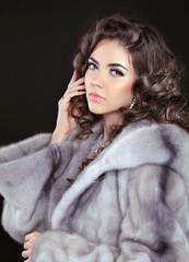 Beautiful brunette woman in mink fur coat isolated on black back