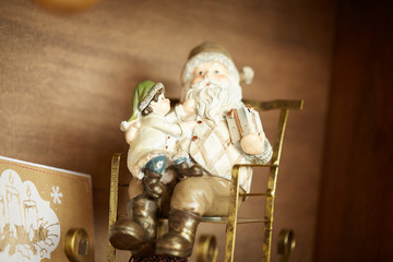 Toy Santa with a gnome in a rocking chair on the shelf