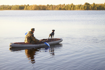The hunter with an okhotnchy dog floats by the boat