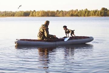 The hunter with a dog in the boat in the middle of the lake