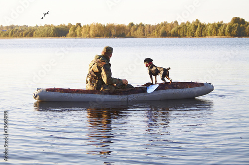 Fotobehang Jacht The hunter with a dog in the boat in the middle of the lake