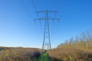 Transmission tower under a sunny sky at fall